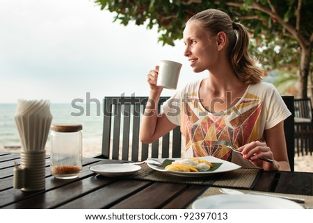 A young and attractive woman having a mango dessert in an outdoor restaurant on a beach - stock photo