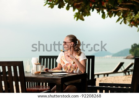 A young and attractive woman having a meal in an outdoor restaurant on a beach - stock photo
