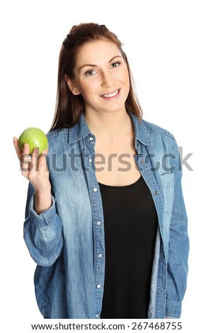 A young and attractive woman in her 20s wearing a blue jeans shirt holding a green apple. White background. - stock photo