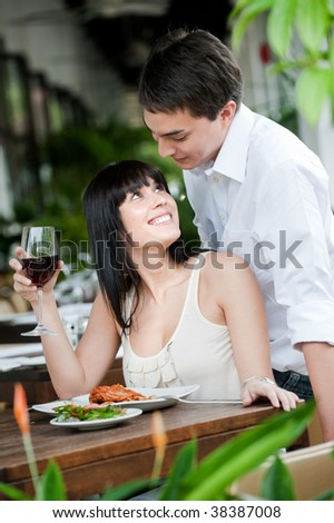 A young and attractive woman is surprised by her partner while dining in an outdoor restaurant - stock photo