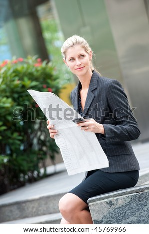 A young and attractive woman reading newspapers - stock photo