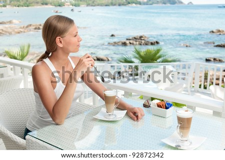 A young and attractive woman sitting on a gallery in an modern outdoor ocean viewpoint restaurant - stock photo