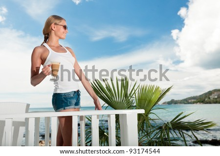 A young and attractive woman stand on a gallery in an modern outdoor ocean viewpoint restaurant - stock photo