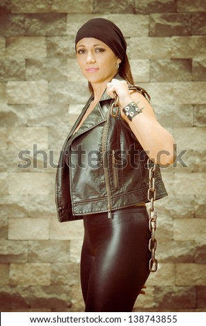 A young and beautiful latina gang woman in leather - stock photo