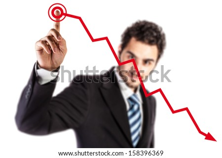 a young and handsome businessman touching a descending red financial graph - stock photo