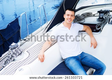 A young and handsome Caucasian man relaxing on the deck of a boat on the sea. - stock photo