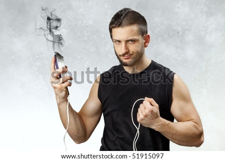 A young and handsome man with a broken and exploded clipper in his hand which left him half shaved and trimmed. The concept of do-it-yourself accidents and disappointment/frustration. - stock photo