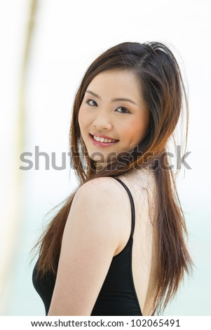 A young and happy Asian lady at the beach