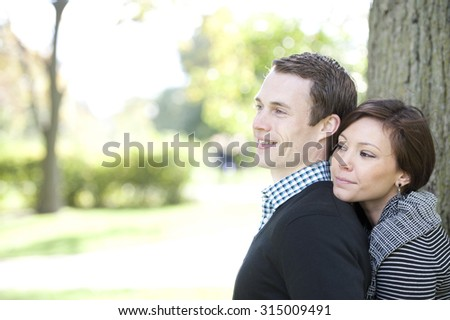 A young and happy couple looking to the left with room for copy space. - stock photo