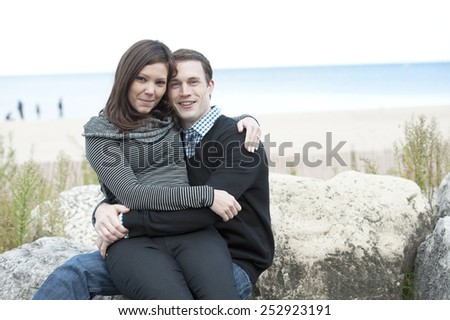 A young and happy couple posing with a beach in the background. - stock photo