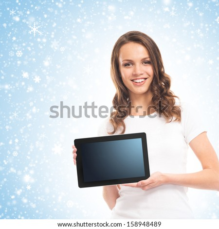 A young and happy girl holding a tablet computer over Christmas background with snowflakes - stock photo