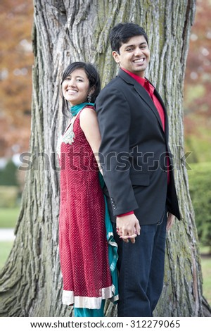 A young and happy Indian couple posing back to back in front of a tree in the fall on a cloudy day. - stock photo