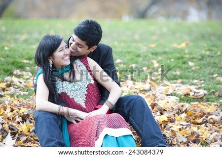 A young and happy Indian couple posing on a pile of leaves in the fall on a cloudy day. - stock photo