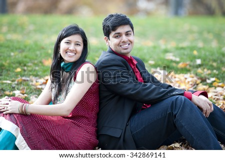 A young and happy Indian couple sitting on leaves back to back in the Fall on a cloudy day.