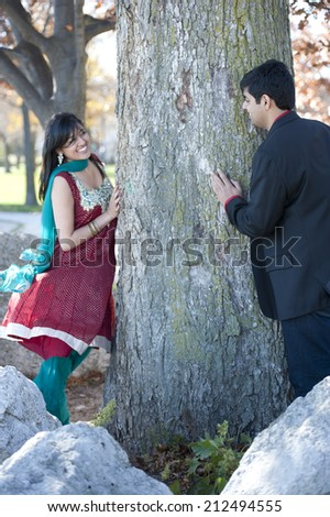 A young and happy Indian couple wearing traditional attire looking for each other around a tree. - stock photo