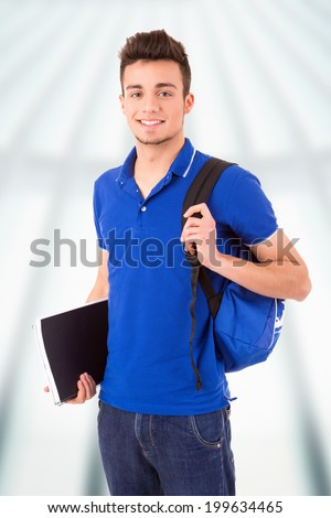 A young and happy student with books and backpack posing - stock photo