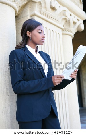 A young and pretty african american woman at college reading newspaper - stock photo