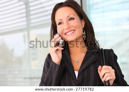 A young and pretty business woman on phone at office - stock photo