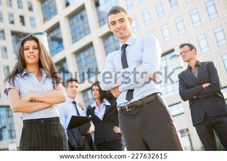 A young and pretty businesswoman and businessman with their team in the background standing in front of the company by looking at the camera and smiling. - stock photo