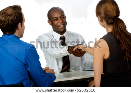 A young and professional businessman shaking hands and securing a deal in his office