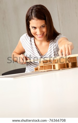 A young architect designing and building a model house - stock photo