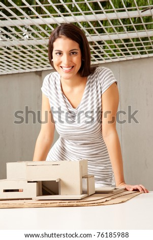 A young architect looking at the camera smiling with a rough model house - stock photo