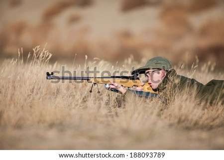 A young army cadet laying in the dry grass target shooting. - stock photo