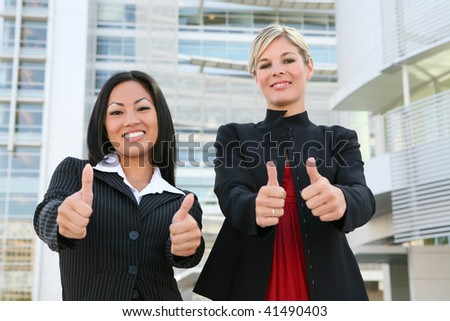 A young asian and caucasian business woman team celebrating a success - stock photo