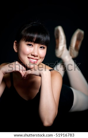 A young asian ballerina posing with her chin on her hands, against black background - stock photo