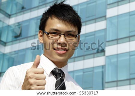 A young Asian business executive showing the thumbs up - stock photo