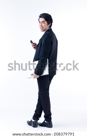 A young asian business man standing with laptop and phone - stock photo