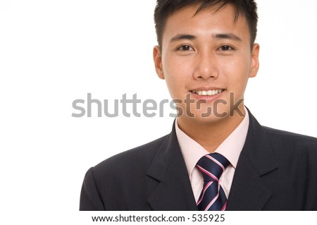 A young asian businessman in a sharp navy blue suit with matching pink shirt and tie