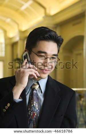A young Asian businessman in an upscale hotel smiles with a mobile phone to his ear. Horizontal shot.
