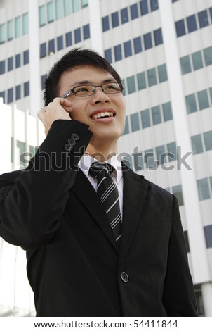 A young Asian businessman speaking on the phone - stock photo