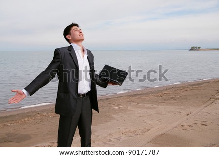 A young Asian businessman standing on the beach. He has a laptop in hand. He enjoys the freedom.