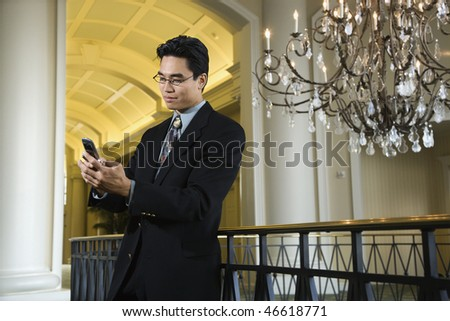 A young Asian businessman types on his mobile phone in an upscale hotel. Horizontal shot.