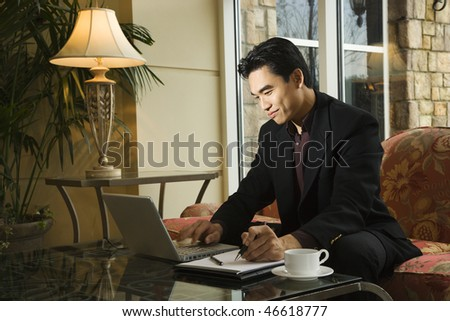 A young Asian businessman typing on a laptop computer whiles taking notes on a notebook. Horizontal shot. - stock photo