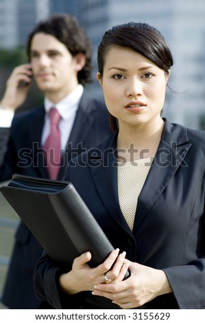 A young asian businesswoman holding document folder with male colleague standing behind (shallow depth of field used)