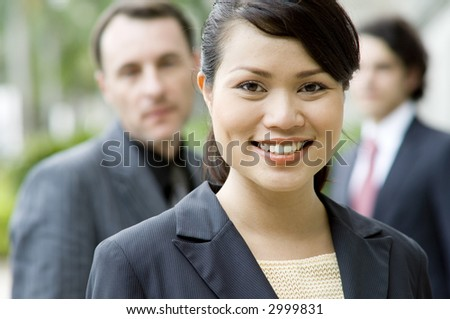 A young asian businesswoman standing in front of her team (shallow depth of field used)