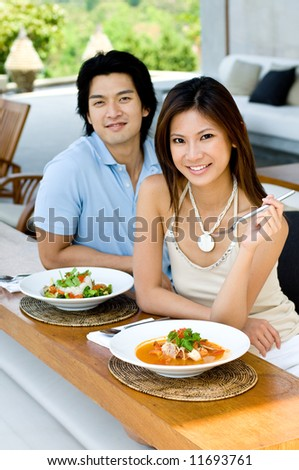 A young Asian couple enjoying lunch outdoors - stock photo