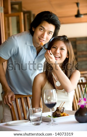 A young Asian couple having dinner at a restaurant - stock photo