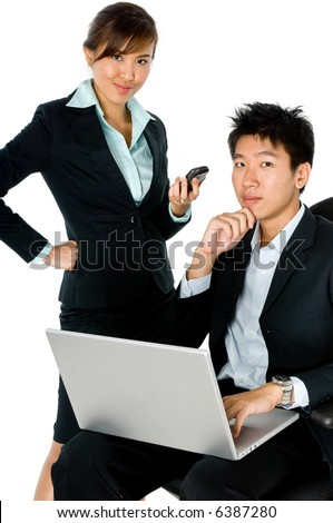 A young Asian couple in business attire working together on laptop computer on white background