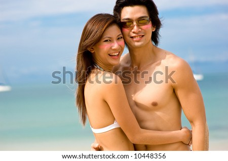 A young Asian couple on beach with ocean behind