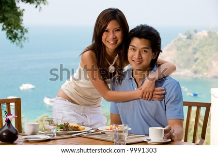 A young Asian couple sitting at the breakfast table outside with the ocean behind them