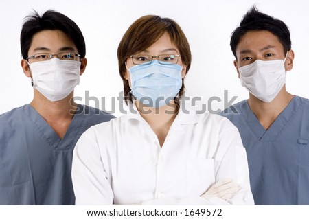 A young asian female doctor is flanked by two men in scrubs