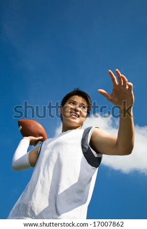 A young asian football player throwing a football - stock photo