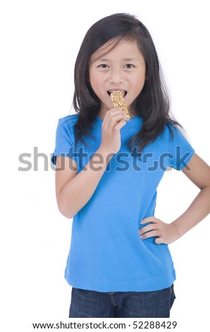A young Asian Girl eating a granola bar - stock photo
