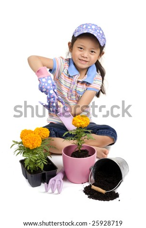 A young Asian girl plants a Marigold in a pot. - stock photo