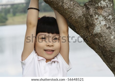 A young Asian girl playing around a tree
