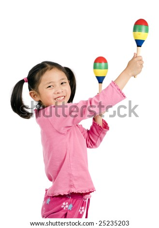 A young asian girl playing maracas - stock photo